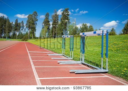 Hurdles Stacked At The Edge Of Running Track
