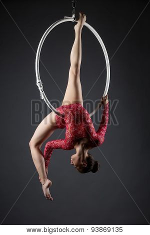 Sexy female acrobat exercising with hanging hoop