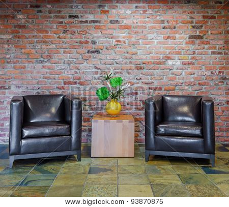 Detail of living room sitting area against brick background.
