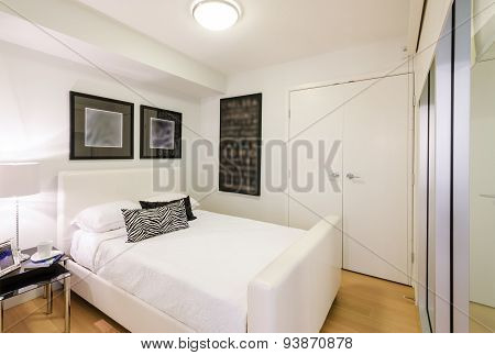Modern bedroom interior design with black pattern designer pillow accents in a luxury house.