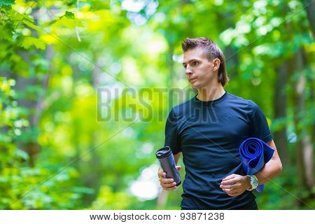 Young active man with mat for meditation and bottle of water after jogging outdoors