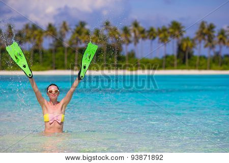 Travel beach fun concept - woman holding snorkeling fins standing in turquiose water