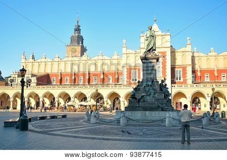 The statue of Adam Mickiewicz and Cloth Hall (Sukiennice) on the main square in Krakow.