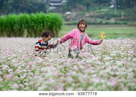Two kids in a buckwheat (tam giac mach) flower field in Hagiang, Vietnam