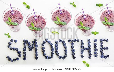 Blueberry Smoothie In A Glass Jar With A Straw And Sprig Of Mint, With Fresh Berries