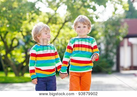 Two Little Brothers Children In Colorful Clothing Walking Hand In Hand