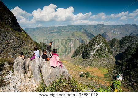 Ethnic minority children sit near mountains in Hagiang, Vietnam