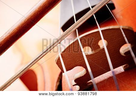 Close Up Of Bow Playing Strings Over Violin Bridge