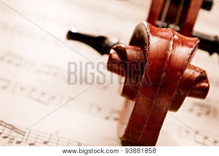 Carved Wooden Violin Scroll Resting On Sheet Music