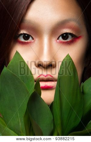 Beautiful Asian girl with a bright make-up art in green leaves. Beauty face. Creative image.