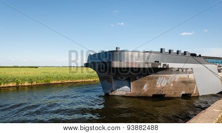 Big Ship In A Narrow Canal Surrounded By A Rural Landscape