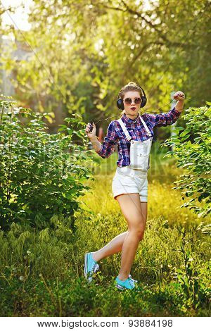 Hipster Girl With Headphones And The Player Is Dancing In The Park.