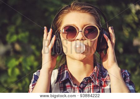 Hipster Girl Listening To Music On Headphones And Chews The Cud.