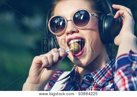Hipster Girl Listening To Music On Headphones With Lollipop.