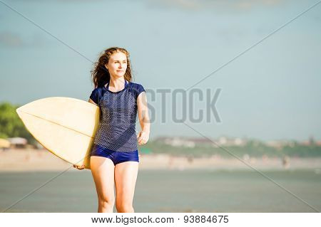 Beautiful sexy surfer girl on the beach at sunset walks along ocean shore, yellow surfboard in her h