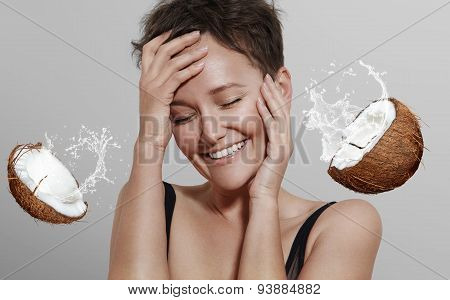Happy Laughing Girl On A Grey Background With A Coconut Spread  A Milk