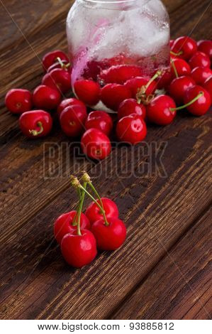 Four Cherries On Wooden Board In Front Of Others