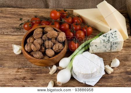 Three Kinds Of Cheese And Various Vegetable On Wooden Board
