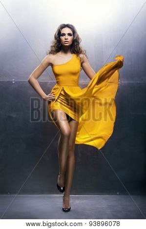 Beautiful and sexy young girl in a yellow dress over an iron background