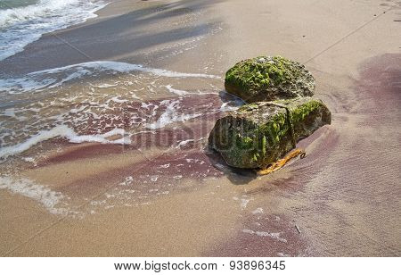 Boulders with green moss in red sand