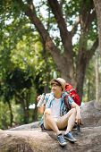 pic of thermos  - Vietnamese traveller sitting on the tree trunk and drinking tea from the thermos - JPG