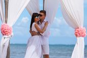 pic of wedding arch  - young loving couple on their wedding day beautiful wedding arch on beach outdoor beach wedding in tropics - JPG