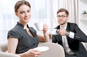 picture of psychologist  - Young man wearing a black suit sitting on a couch drinking tea and talking friendly with his psychologist during therapy session - JPG