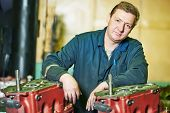 image of assemblage  - industrial worker assembler portrait with gearbox utits at manufacture workshop - JPG