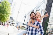 image of piggyback ride  - Happy woman showing something to man while enjoying piggyback ride in city - JPG