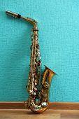 image of saxophones  - Saxophone on turquoise wallpaper background - JPG