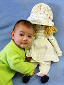 picture of baby doll  - Portrait of a smiling baby boy with a doll on a blue towel  - JPG