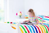 foto of little young child children girl toddler  - Toddler girl reading a book in bed - JPG
