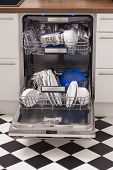 foto of dishwasher  - Dishwasher loades in a kitchen with clean dishes and blue light - JPG