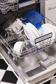 picture of dishwasher  - Dishwasher loades in a kitchen with clean dishes and blue light - JPG