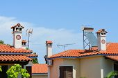 stock photo of chimney  - Typical Greek roofs with decorative chimneys and solar panel - JPG