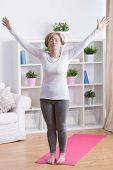 stock photo of breath taking  - Senior woman taking deep breath during morning yoga - JPG