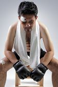 foto of jiujitsu  - Portrait of exhausted MMA fighter sitting on a wooden chair on grey background - JPG