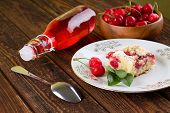 picture of fruit bowl  - Horizontal photo with white plate with two cherries herb leaves and portion of fruit cake - JPG