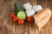 picture of baguette  - Horizontal photo of wooden board with four red cherry tomatoes three whole garlic heads and half of green cucumber - JPG