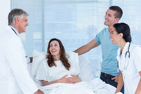 stock photo of hospital gown  - Future parents talking with smiling doctors in hospital room - JPG
