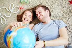 stock photo of globe  - Young couple with globe dreaming of summer vacations - JPG