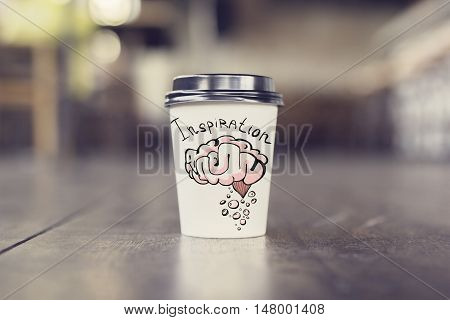 Takeaway coffee cup with brain sketch on wooden floor. Inspire concept