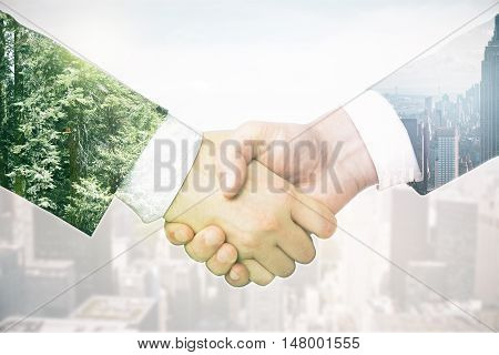 Closeup of businesspeople's handshake on abstract light background with city and forest. Double exposure. Business concept