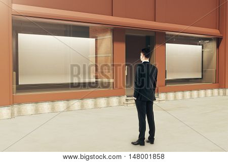 Confident businessman looking at showcase with large billboards in daylight. Mock up 3D Rendering