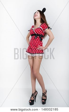 Beautiful young leggy brunette in a very short red dress with white polka dots on the legs black high-heeled shoes. full height.