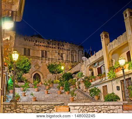 TAORMINA ITALY - OCTOBER 1 2012: The evening view of Ciampoli Palace and the tiny garden on its staircase on October 1 in Taormina.