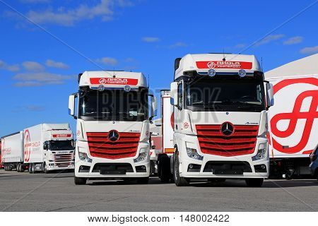 NAANTALI FINLAND - SEPTEMBER 16; 2016: Fleet of new Mercedes-Benz Actros and Scania cargo trucks on display against blue sky on the Open Doors Event of Ahola Transport in Naantali Finland.