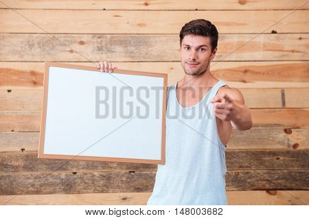 Happy casual man holding blank board and poiting finger at camera over wooden background
