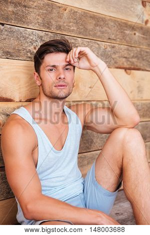 Pensive casual young man relaxing while sitting on the floor over wooden background
