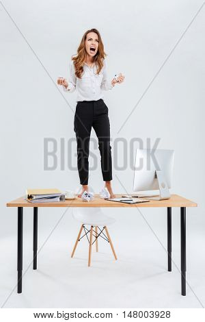 Angry mad young businesswoman standing on table and screaming over white background